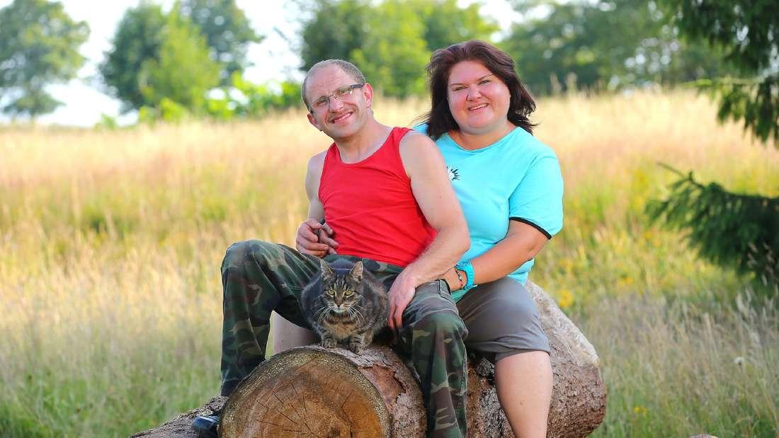 Steffen und Nicole sitzen auf einem Baumstamm
