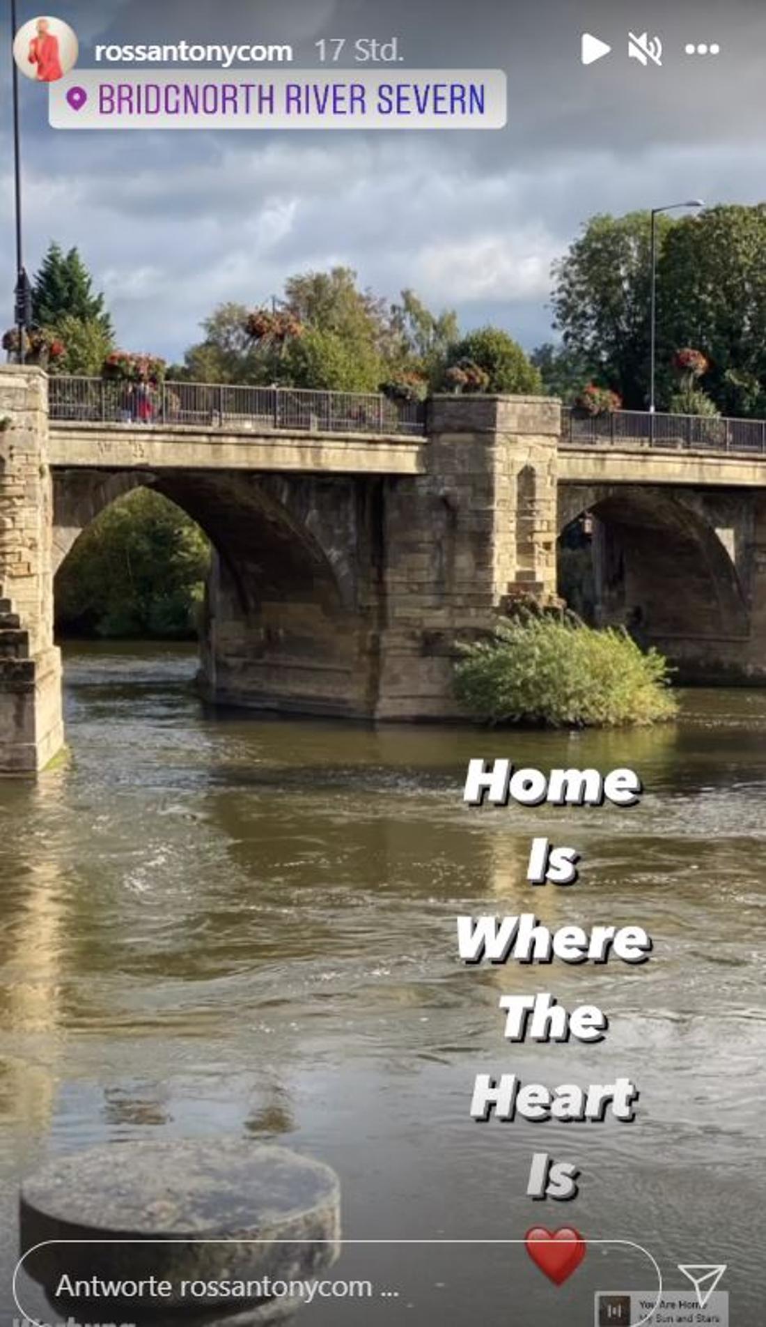 """""""Home is where the heart is"""" (ZuHause ist da, wo das Herz ist). Im Hintergrund ein Fluss mit einer Brücke"""