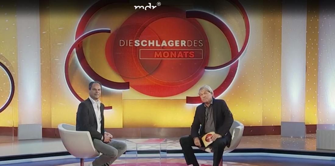 Bernhard Brink und Musikexperte Mathias Giloth sitzen im Studio und schauen in die Kamera